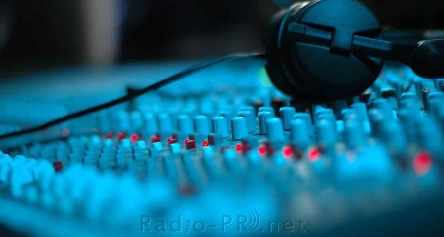 Bild eines Mischpultes in der Seitenansicht, ein Kopfhörer liegt auf den Reglern. Die Oberfläche des Mischpoultes verliert sich nach hinten im Unscharfen. Die Grundfarbe ist ein intensives Cyanblau.