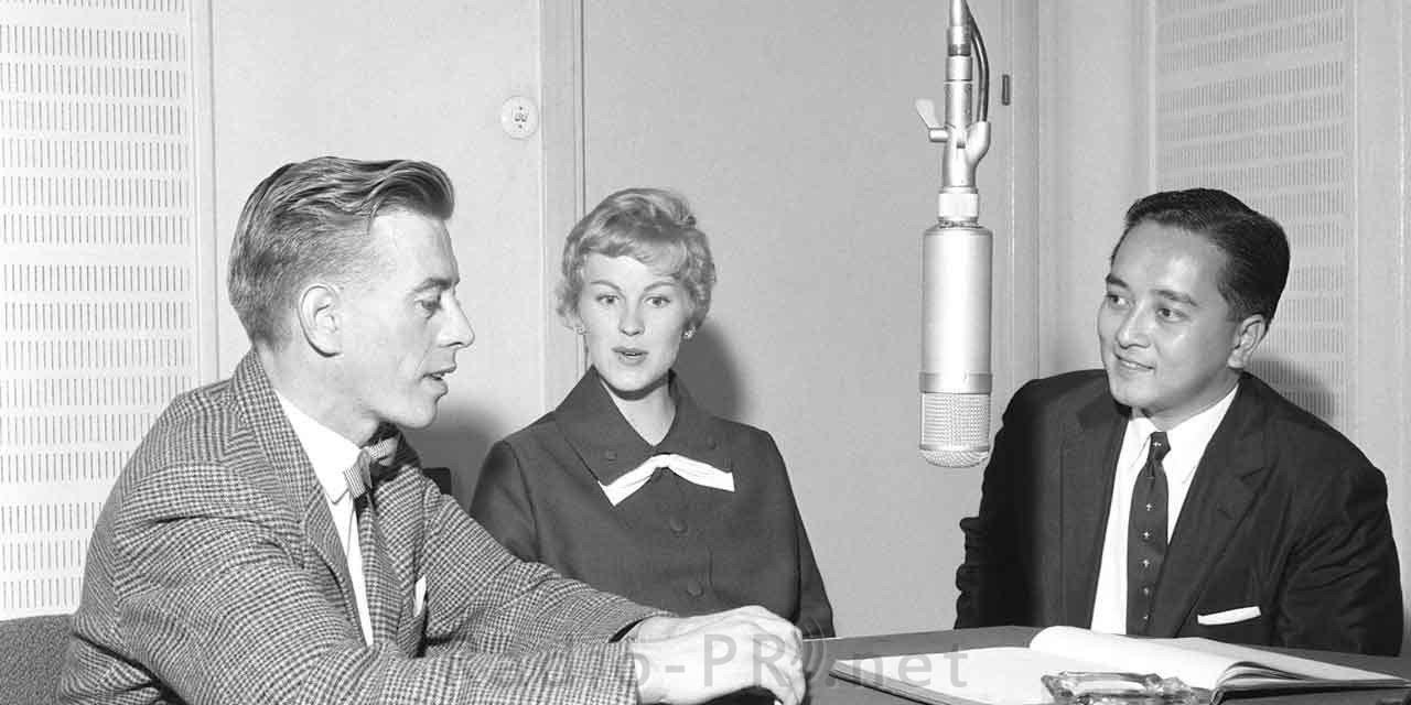 Radiointerview-Situation in schwarzweiss - zwei Männer und eine Frau sitzen in einem Rundfunkstudio